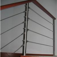 Barandilla realizada con pilastras de tubo de 50 pulido brillo y cables trenzados intermedios con tensores en las puntas. Pasamanos en madera